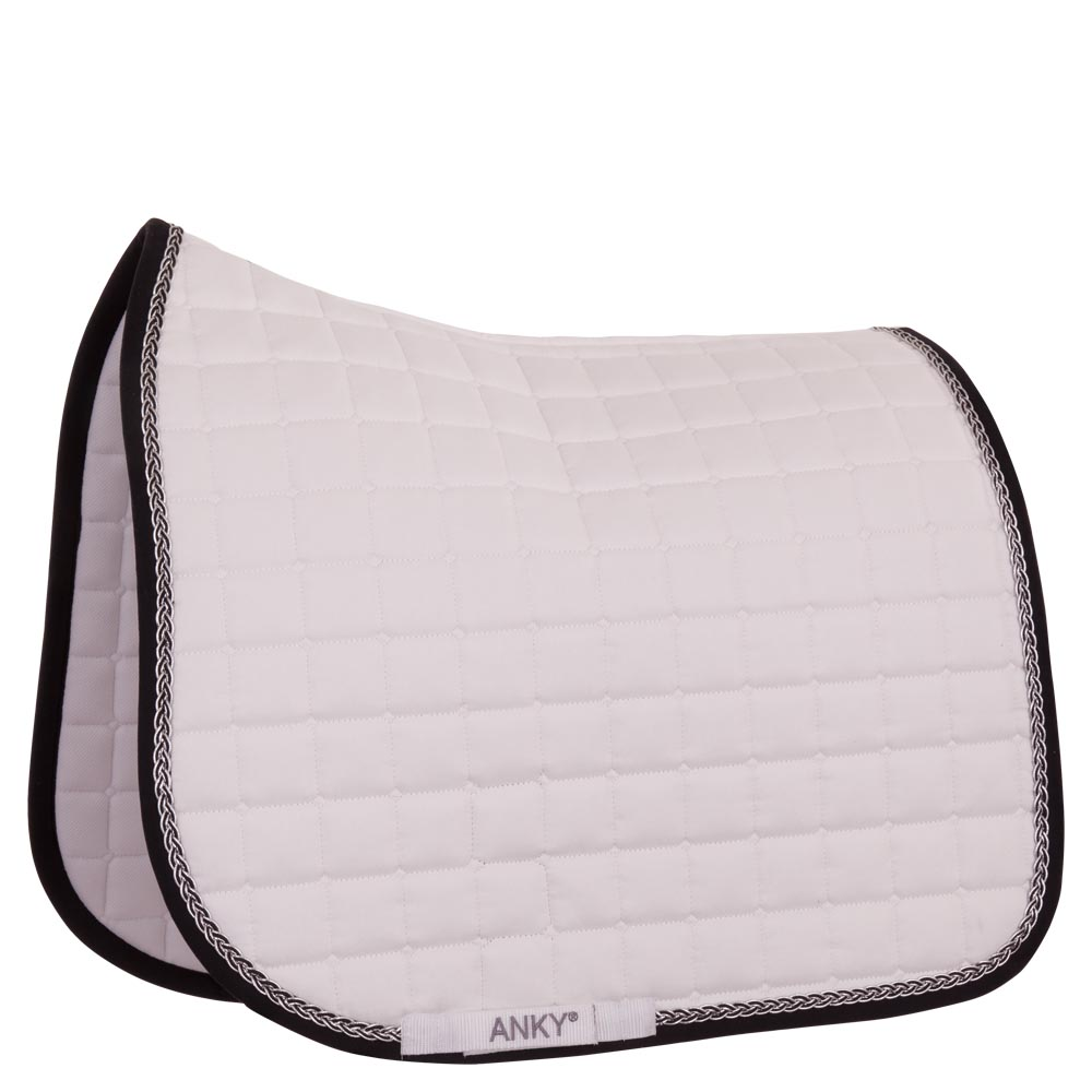 <i>This delightful ANKY® saddle pad is perfect for shows and competitions!</i><br><br>This anatomically shaped saddle pad is made of 100% combed cotton lined with Coolmax®. This material is known for its excellent moisture regulating and breathable properties. The saddle pad features a comfortable padding made of fiberfill and felt. The pad has a square quilt design and its piping is embellished with a luxurious braided cord with silver thread for a shiny touch. The uncovered corners of the saddle pad are a convenient spot for sponsor logos. The pad has girth loops with Velcro and can be put in the washing machine at 30°C.<br><br>Looks especially beautiful when combined with the ANKY® ear bonnet Braided, item A37402.